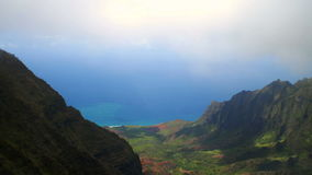 Clouds moving over lush valley overlooking na pali coast. Video of clouds moving over lush valley overlooking na pali coast stock video