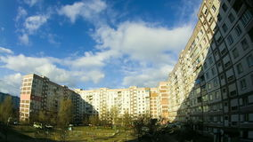 Clouds Moving over the Multistorey Buildings Time Lapse. Yard in the city with high-rise buildings over which the clouds moving in the sky. ULTRA HD 3840 x stock video