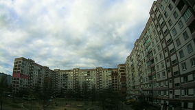 Clouds Moving over the Multistorey Buildings Time Lapse. Yard in the city with high-rise buildings over which the clouds moving in the sky. ULTRA HD 3840 x stock video footage