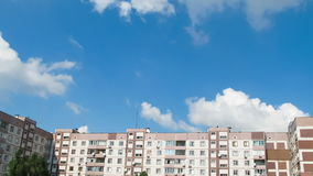 Clouds Moving over the Multistorey Buildings Time Lapse. Yard in the city with high-rise buildings over which the clouds moving in the sky. Full HD 1920 x 1080 stock footage