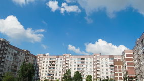 Clouds Moving over the Multistorey Buildings Time Lapse. Yard in the city with high-rise buildings over which the clouds moving in the sky. Ultra HD 4K, 3840 x stock footage