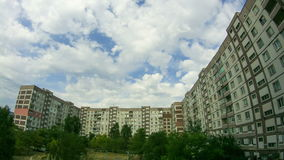 Clouds Moving Over The Multistorey Buildings. Time Lapse. Clouds Moving Over The Multistorey Buildings. Yard in the city with high-rise buildings over which the stock video footage