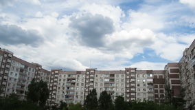 Clouds Moving Over The Multistorey Buildings. Time Lapse. Clouds Moving Over The Multistorey Buildings. Yard in the city with high-rise buildings over which the stock footage