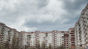 Clouds Moving over the Multistorey Buildings Time Lapse. Yard in the city with high-rise buildings over which the clouds moving in the sky. ULTRA HD 3840 x 2160 stock video