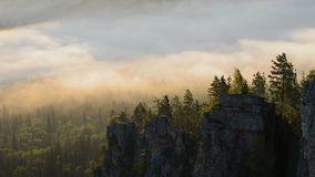 Clouds moving over pine tree highland forest and rocks. Foggy morning landscape at Ural mountains. Clouds moving over pine tree highland forest. Foggy morning stock video footage