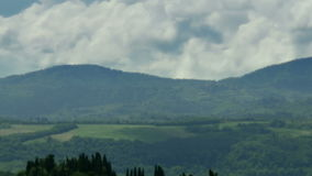 Clouds moving over Tuscany Landscape. Static medium long high angle high dynamic range time lapse shot of clouds and shadows of clouds moving over a landscape of stock footage