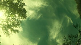 Clouds are moving the view from under the water. Underwater camera in the river, bottom view of the sky and the movement of the clouds and trees. Time lapse stock footage