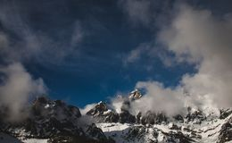 Clouds Near Snow Covered Mountains Royalty Free Stock Image