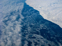 Clouds, ocean and Greenland coastline. Aerial view of the Greenland costline and adjacent ocean with clouds royalty free stock image