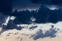 Clouds off to the dance. Chunky, smoky cumulus clouds in a contrasty sky at sundown Royalty Free Stock Photography