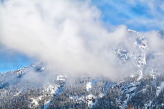 Clouds over alpine winter peaks Royalty Free Stock Photography