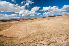 Clouds over the arid landscape in a valley with a dried ground. White clouds float over the arid landscape in a valley with a dried ground in the Middle East Royalty Free Stock Image