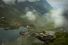 Clouds over Balea Lake. Lodge cabin on beautiful location Stock Image