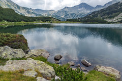 Clouds over Banderishki chukar peak and Reflection in Muratovo lake, Pirin Mountain Royalty Free Stock Photo