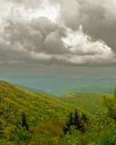 Clouds Over the Blue Ridge Mountain. The sun peeks through clouds to shine over a bright green valley in the Blue Ridge Mountains royalty free stock images