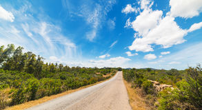 Clouds over an empty country road Royalty Free Stock Photos