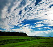 Clouds over field. Clouds over the river surrounded by great green banks. Blue, crisp sky is wide opened filled with great white puffy clouds. After the rain Royalty Free Stock Images