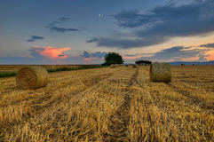 Clouds over field with hay. Sunset on the harvested field with bales Stock Photography