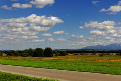 Clouds over the field on a sunny day. And mountains on background Royalty Free Stock Images