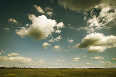 Clouds over the green field. Stock Photos