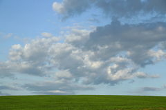 Clouds over the green field on a Sunny day Royalty Free Stock Photography