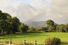 Clouds over the green lawn in Aghadoe area Stock Photos