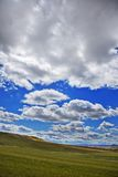 Clouds over a hill Stock Photos