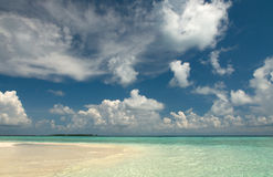 Clouds over Indian Ocean. White clouds and golden sand of Vilamendhoo island royalty free stock images