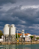 Clouds over industrial harbor. Dark clouds over industry river harbor with silos Stock Photography