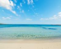 Clouds over La Pelosa beach. Blue sea in La Pelosa beach, Sardinia Royalty Free Stock Image