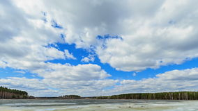 Clouds over the lake. Last snow. Fixed geometry Stock Photography