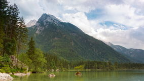 Clouds over the Lake and Mountains. Time Lapse UHD. Germany. Lake Hintersee. Clouds quickly fly over the mountains. Light and shade from the sun on the forest stock video footage