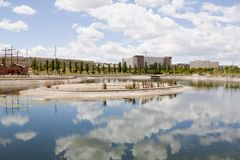 Clouds over a lake, a park and an urbanization. In Zaragoza Royalty Free Stock Image