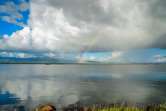 Clouds over lake reflection in water and rainbow Royalty Free Stock Image
