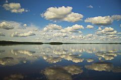 Clouds over the lake on a summer day. The reflection on the water Royalty Free Stock Image