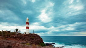 Clouds over lighthouse on rocky tropical island timelapse stock footage
