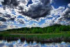 Clouds Over A Marsh. Afternoon clouds temporarily block the sun over a marsh Royalty Free Stock Photos