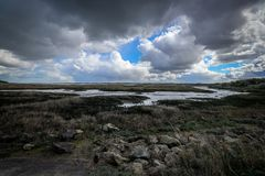 Clouds over the marshes. Dramatic view of clouds forming across the marshes on the Kent coastline in England stock images