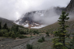 Clouds over Mount Edith Cavell in Canadian Rockies. Mount Edith Cavell visible though the morning fog with a stream in the foreground. Jasper National Park royalty free stock photos