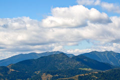 Clouds over mountain peaks. Landscape of clouds over mountain peaks during summer sunny day Stock Photos