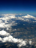 Clouds over mountains. View of clouds over mountains from an airplane Royalty Free Stock Image