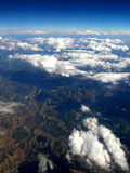 Clouds over mountains. View of clouds over mountains from an airplane Stock Photography