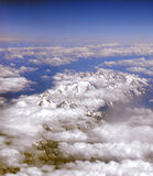 Clouds over mountains. View of clouds over mountains from an airplane Royalty Free Stock Photography