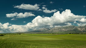 Clouds over the mountains and green field of wheat in Kazakhstan - 4K Timelapse stock video footage