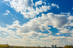 Clouds over park from the city and office buildings in the backg. Round. Beautiful blue sky royalty free stock images