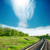 Clouds over railroad in green landscape Stock Photo