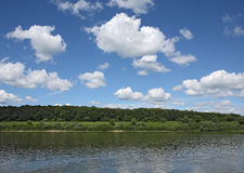 Clouds over river. White clouds on blue sky over river stock photo
