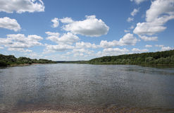 Clouds over river. White clouds on blue sky over river (wide angle stock images