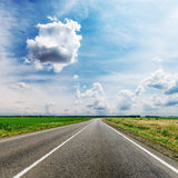 Clouds over road in fields Stock Photos