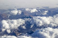 Clouds over rocks and mountains. View from an airplane during a journey and flight Royalty Free Stock Image